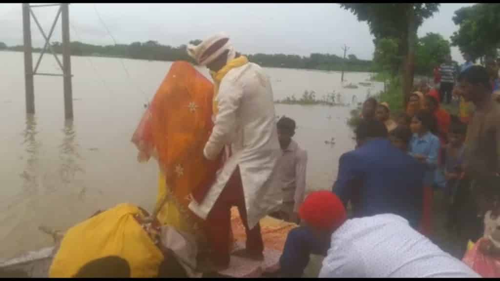 In flood effected Araria, bride and groom crosses water using containers